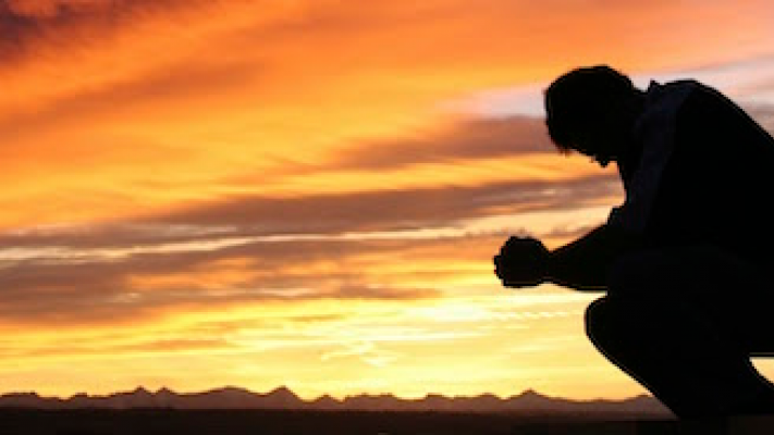 Photo of a figure silhouetted against a sunset kneeling in prayer